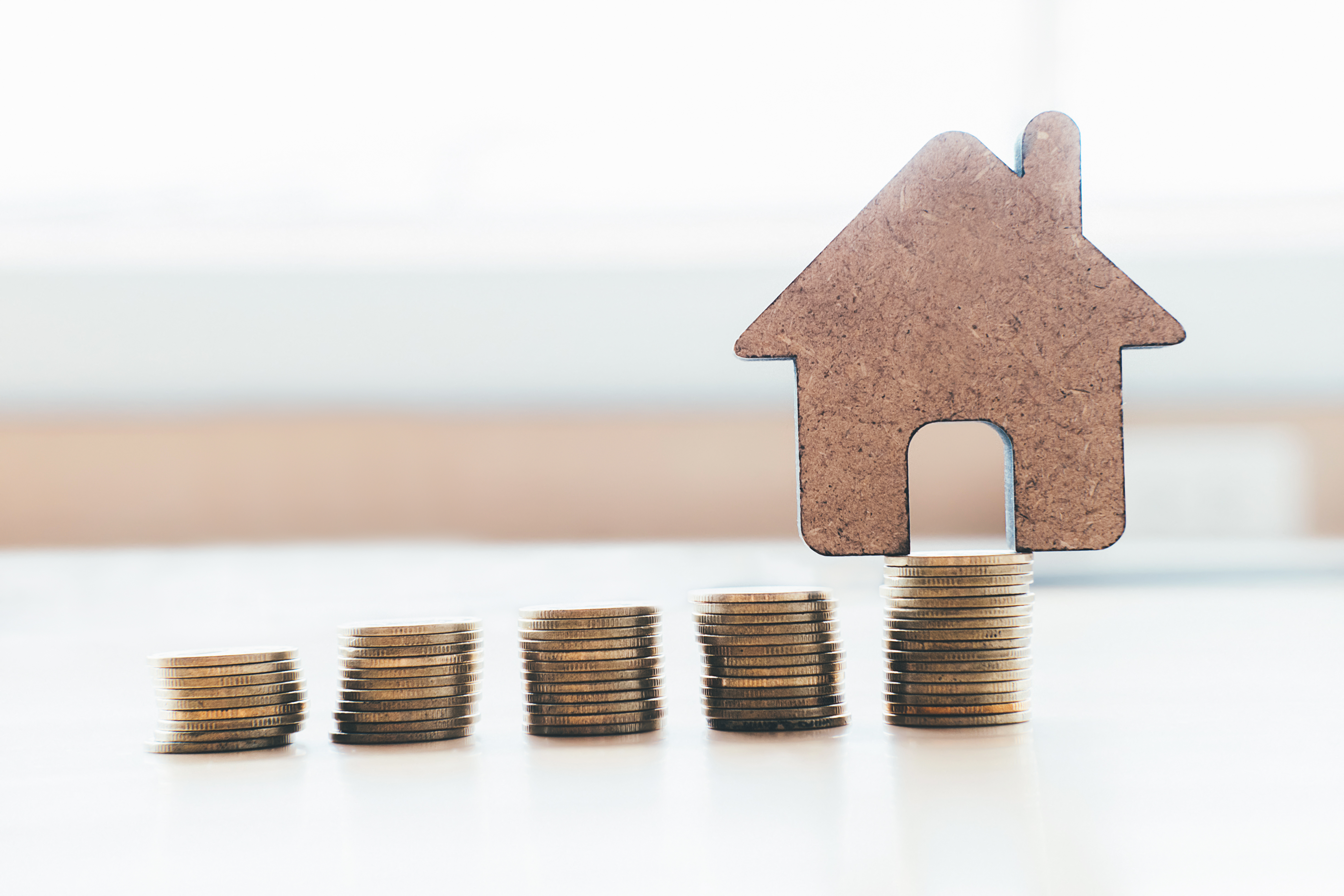 Soft focus of House and Golden Coins Stacks with blur Background.Savings Plans for Housing,Finance and Banking about House concept.